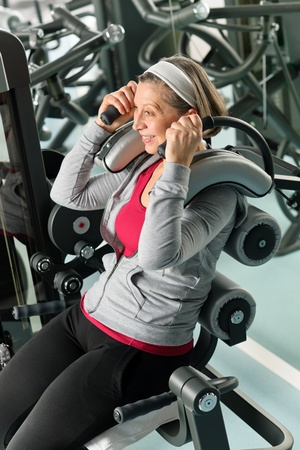 leisure centre: Fitness center senior woman exercise smiling on gym machine Stock Photo