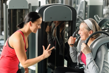 aide � la personne: Centre de fitness femme �g�e d'exercer les muscles abdominaux avec un entra�neur personnel