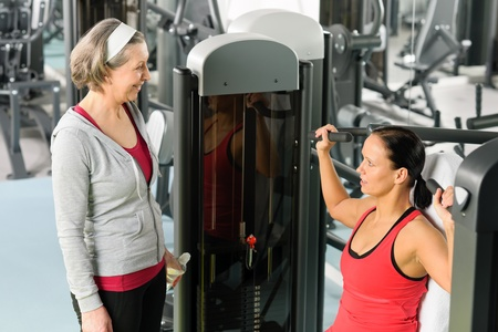 Personal trainer at fitness center showing exercise to senior woman photo