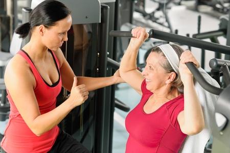 hombros: Entrenador personal ayudar a la mujer mayor ejercicio en la m�quina en el gimnasio