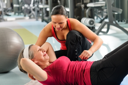 abdomen fitness: Gimnasio mujer mayor ejercicio con entrenador personal en el tapete