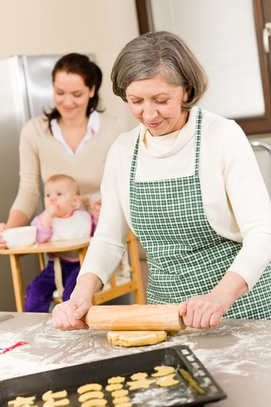 Senior woman rolling dough prepare for baking cookies in kitchen photo