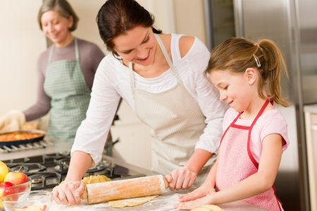 Young girl prepare apple pie baking with mother and grandmother photo