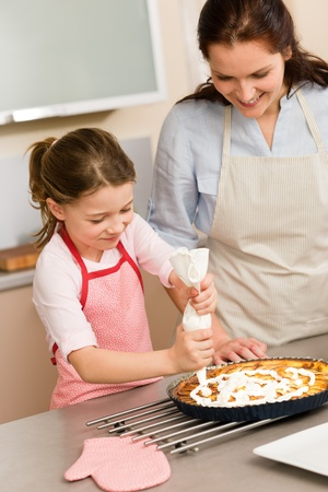 Mother and daughter decorating apple pie with whipped cream Stock Photo - 12756902