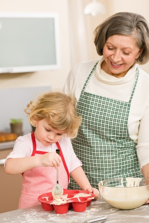 grandmas: Woman and little girl make cupcakes together fill baking form