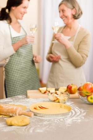 Apple pie baking two women drink wine together in kitchen Stock Photo - 12758292