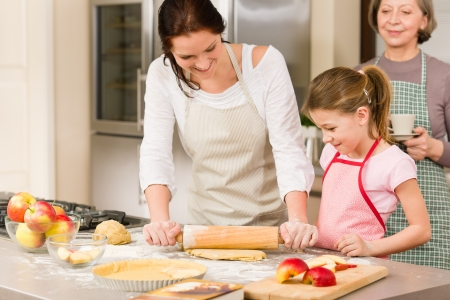 Mother and daughter making apple pie together grandmother check recipe Stock Photo - 12758325