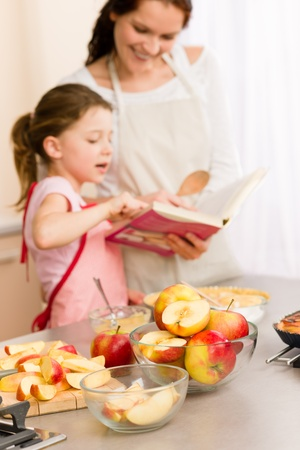 Apple pie mother and daughter follow recipe from baking cookbook Stock Photo - 12758293