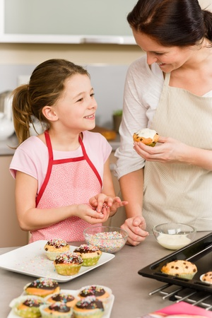 Mother and daughter decorating cupcakes sprinkles happy together at home Stock Photo - 12758330
