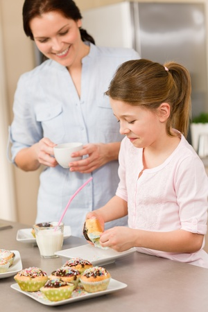 Little girl taste sprinkles cupcakes with mum happy at home Stock Photo - 12758301