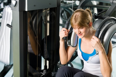 Fitness center young woman exercise abdominal muscles on gym machine photo
