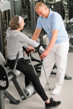 physical: Senior woman with crutches getting help of physiotherapist at gym