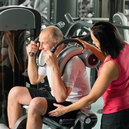 Mature man exercising at gym under supervision of personal trainer photo