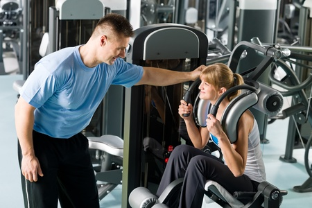 fitness instructor: Fitness center young woman exercise with personal trainer on gym machine