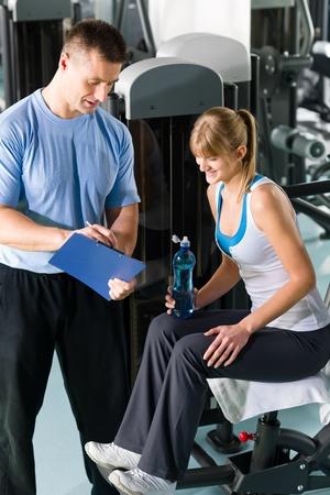 aide � la personne: Jeune femme avec un regard entra�neur personnel � tableau d'exercices au gymnase Banque d'images