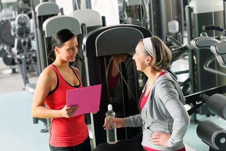 aide à la personne: Senior femme avec un entraîneur de discuter du plan personnel au gymnase