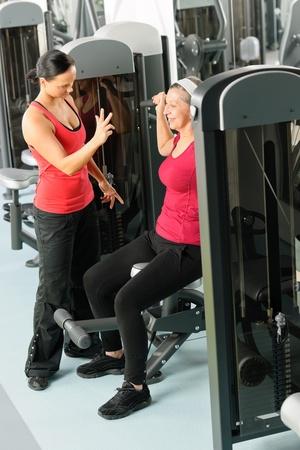 Mujer feliz senior de entrenamiento de gimnasio con entrenador personal de asistencia