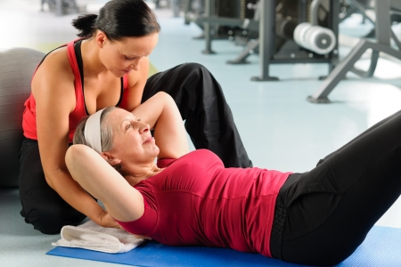 personal trainer woman: Fitness center senior woman exercise with personal trainer on mat