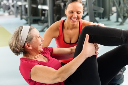 personal trainer: Fitness center senior woman exercise sit ups with personal trainer