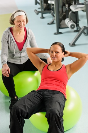 Fitness center senior woman with trainer exercising on swiss ball photo