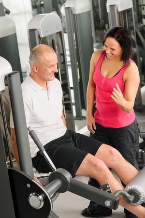 aide � la personne: Centre de fitness homme actif exer�ant jambes avec un entra�neur personnel