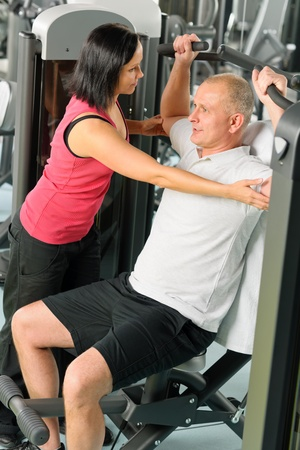 female bodybuilder: Fitness center personal trainer assist man exercise shoulder on machine