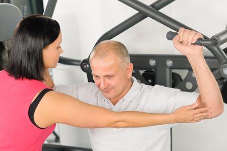 aide � la personne: Centre de fitness assistance entra�neur personnel exercice homme sur la machine de l'�paule