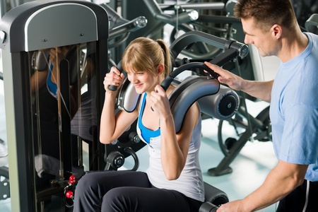 Fitness center young woman exercise with personal trainer on gym machine photo