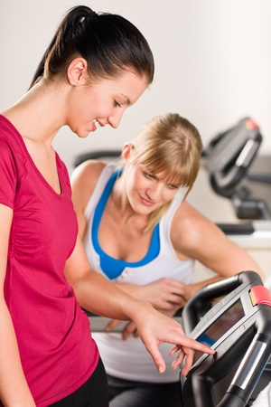 Young women exercising at fitness center on treadmill machine photo