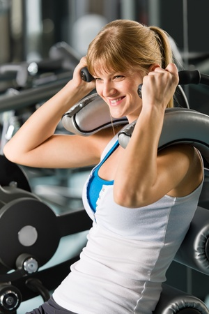 Young woman at fitness center exercise abdominal muscle gym machine photo
