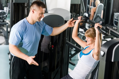 Young woman exercise on shoulder press machine with personal trainer Stock Photo - 12909676