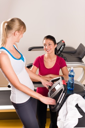 Young woman friends exercising in fitness center on treadmill machine photo