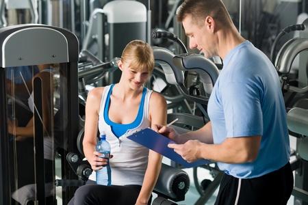 aide � la personne: Jeune femme de remplir le plan personnel de conditionnement physique avec le club formateur en sant�