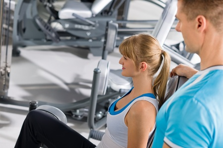 Young woman with personal trainer exercise legs at gym photo