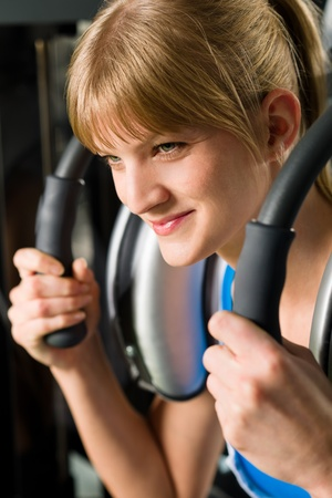 Young woman at gym exercise abdominal muscles on machine photo