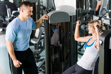 female bodybuilder: Young woman exercise on shoulder press machine with personal trainer