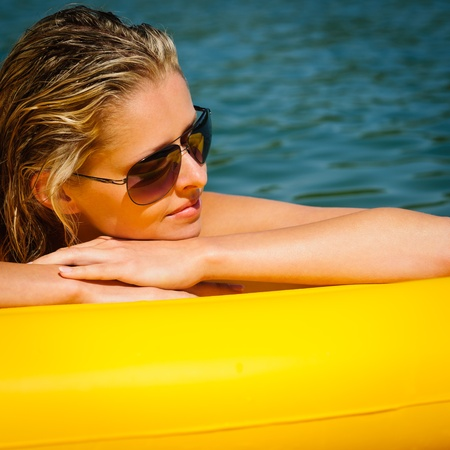 floating on water: Summer woman daydreaming lying on yellow floating mattress close-up