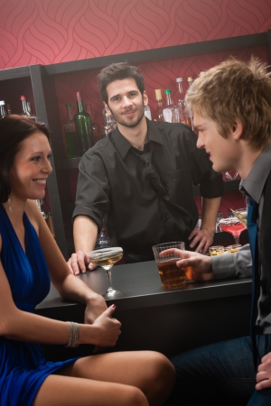 Bartender behind the bar couple chatting and have drink