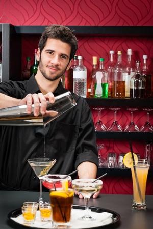 Hermoso barman profesional en el elegante bar de cócteles preparar bebidas