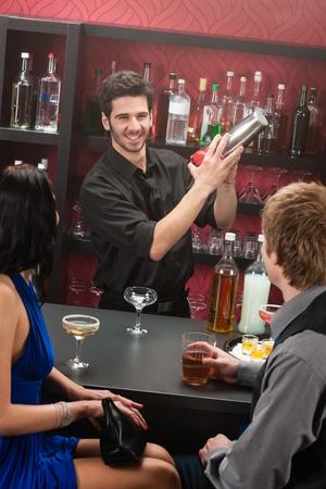 barman: Barman making cocktail for young couple at the bar