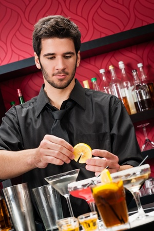Handsome barman professional at posh bar making cocktail drinks photo