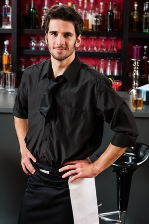 Portrait of handsome barman standing in front of the bar Stock Photo