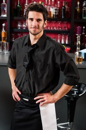 Retrato de apuesto barman, de pie delante de la barra de
