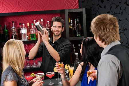 Barman making cocktail for young friends at the bar photo