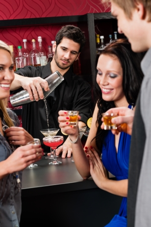 bartender: Barman making cocktail for young friends at the bar