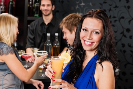 Smiling woman having drink with friends at cocktail bar photo