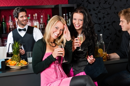 Two smiling girl friends enjoy glass of champagne at bar photo