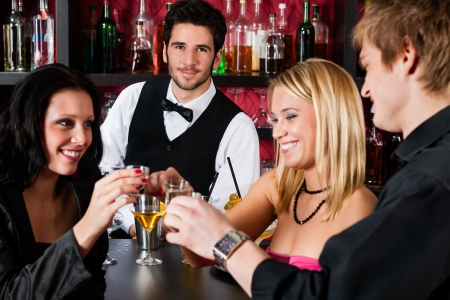 Cheerful barman behind counter with young friends at cocktail bar photo