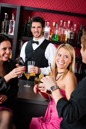 Cheerful barman prepare alcoholic cocktail young friends at the bar photo