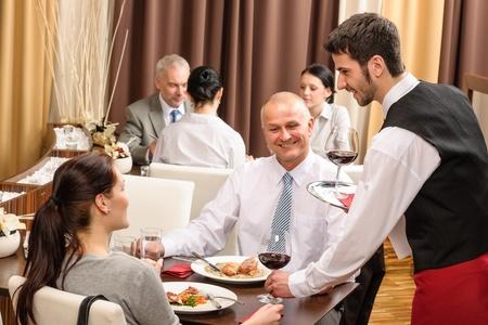 camarero: Joven camarero servir el vino a la gente de negocios en el restaurante de profesionales